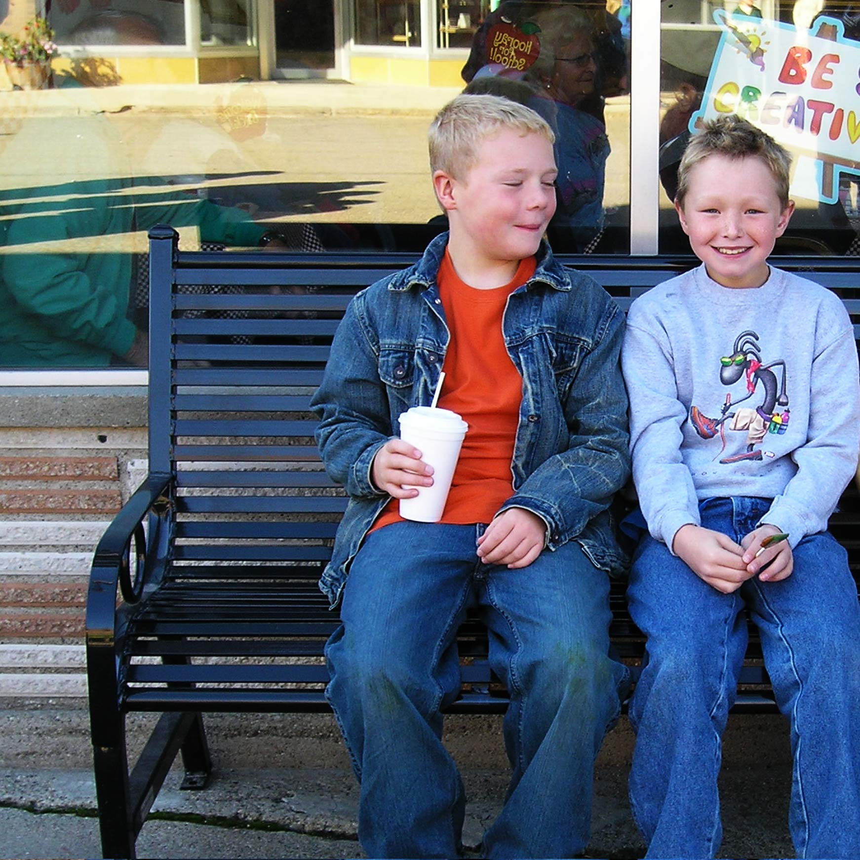 Friends spending time on a donated park bench from OCC Outdoors.